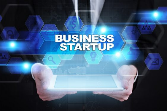 Businessman holding tablet PC with the words 'Business Startup' overlaid