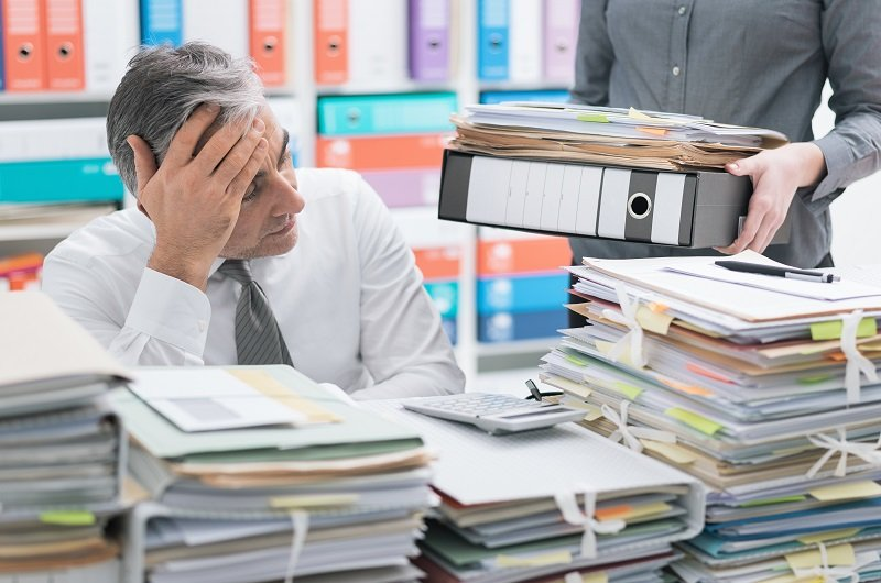Stressed businessman at office desk and overloaded with payroll paperwork, the desktop is covered with payroll paperwork, and his secretary is bringing more files