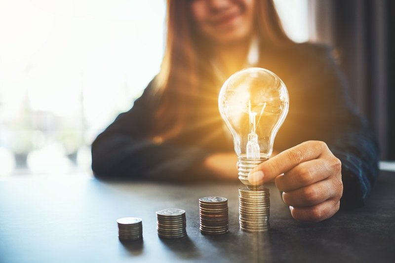 A business woman holding a brightly light bulb on a stack of coins.