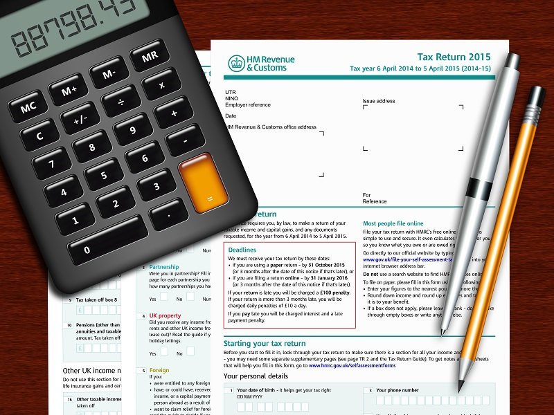 Calculator, pen and pencil on a wooden desk with a HM Revenue & Customs Tax Return form.